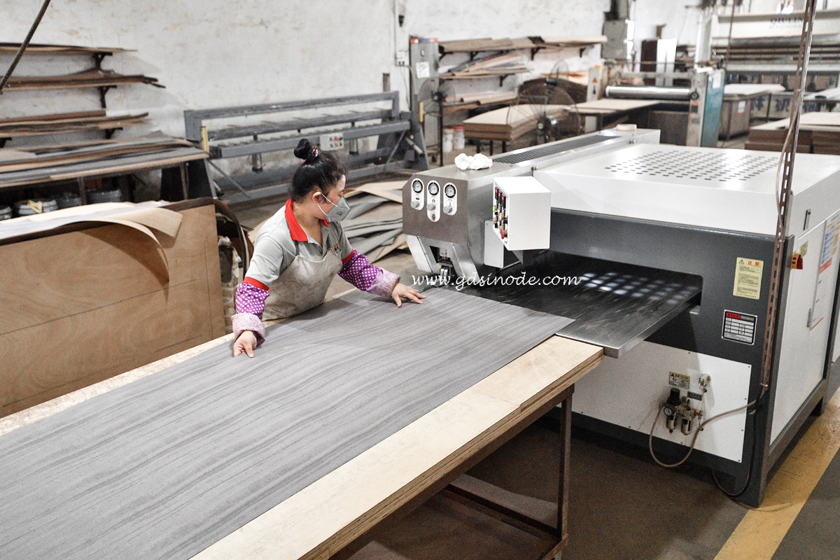 Skilled female worker is sewing veneer